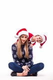 Mutter mit ihrer Tochter im Weihnachtshut Lizenzfreies Stockfoto