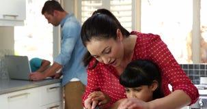 Mutter mit ihrer Tochter kochen, während die Jungen den Computer reparieren stock footage