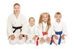 Mutter mit ihrer Tochter und ein Junge mit seiner Schwester, die in einem Karate sitzt, werfen Ritual auf Stockbild