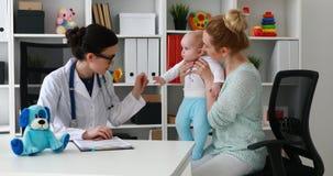 Mutter mit Kind an der Aufnahme der jungen Ärztin stock video