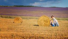Mutter mit Kindern auf dem Feld mit Heu Lizenzfreies Stockbild