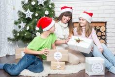Mutter mit Kindern betrachtet Geschenke lizenzfreies stockbild