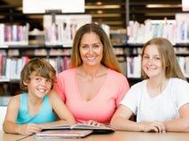 Mutter mit Kindern in der Bibliothek Lizenzfreie Stockfotos