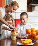 Mutter mit Kindern drückte Orangensaft zusammen Stockfoto