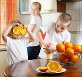 Mutter mit Kindern drückte Orangensaft zusammen Stockbild