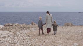 Mutter mit Kindern geht zum Meer stock video