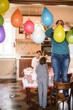 Mutter mit Kindern hängen bunte Ballone für Geburtstagsfeier I Stockfotos