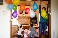 Mutter mit Kindern hängen bunte Ballone für Geburtstagsfeier I Stockfotografie