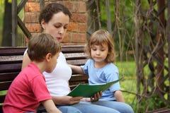 Mutter mit Kindern sitzen und lasen Buch lizenzfreie stockfotos