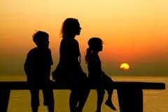 Mutter mit Kindern sitzt auf Bank am Strand Stockbild