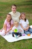 Mutter mit Kindern sitzt auf dem Legen auf Gras Stockfotografie