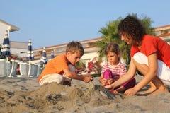 Mutter mit Kindern sitzt auf Strand in der Tageszeit Lizenzfreie Stockfotos