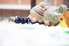 Mutter mit Kinderspiel im Schnee auf Winterweg, positive Gefühle, im Freien Schneefälle, Blizzard Stockfotos