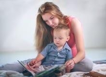 Mutter mit kleinem Babysohn im Raumlesebuch zu Hause stockbild