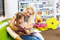 Mutter mit kleinem Mädchen las Buch zusammen stockfoto