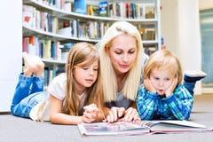 Mutter mit kleinem Mädchen und Jungen las Buch zusammen stockfotografie