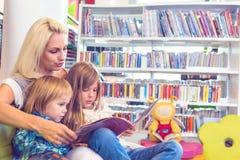 Mutter mit kleinem Mädchen und Jungen las Buch zusammen im Aufenthaltsraum lizenzfreie stockbilder