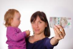 Mutter mit kleiner Tochter hält in der Hand Zloty 500 Stockfotografie