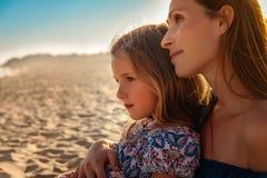 Mutter mit Mädchenuhrsonnenuntergang stockbilder