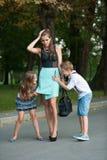 Mutter mit naughti Sohn-ADN-Tochter auf einem Weg im Park Lizenzfreies Stockfoto