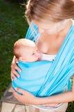 Mutter mit neugeborenem Baby im Riemen stockfotos