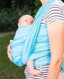 Mutter mit neugeborenem Baby im Riemen stockbild