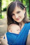 Mutter mit neugeborenem Schätzchen in einem Riemen lizenzfreie stockbilder
