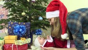 Mutter mit Sankt-Hut mit Säuglingstochter im Weihnachtskleid stock video footage