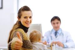 Mutter mit Schätzchen auf Abfrage an Kinderarzt c Lizenzfreies Stockbild
