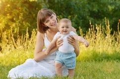 Mutter mit Schätzchen auf grünem Gras Stockfoto