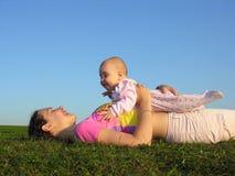 Mutter mit Schätzchen auf Sonnenunterganglüge Lizenzfreie Stockfotografie