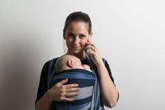 Mutter mit Smartphone und Baby, das im Riemen schläft Schönes Tanzen der jungen Frau der Paare lizenzfreie stockfotografie