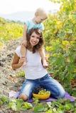 Mutter mit Sohn im Traubenweinberg Stockbild