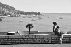 Mutter mit Sonne auf Promenade Monte Carlo, Monaco - 20. September 2015: junge schöne der Mutterfrau mit Sohn sitzen an Lizenzfreie Stockbilder