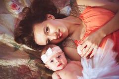 Mutter mit Tochter auf Bett stockbild