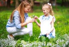 Mutter mit Tochter im gr?nen bl?henden Sommerpark auf Wiese Blumen sammeln stockbilder