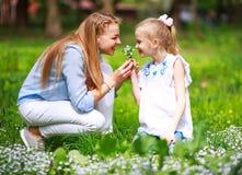 Mutter mit Tochter im gr?nen bl?henden Sommerpark auf Wiese Blumen sammeln stockfotos