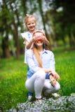 Mutter mit Tochter im gr?nen bl?henden Sommerpark auf Wiese Blumen sammeln stockfoto