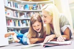 Mutter mit Tochter las Buch zusammen in der Bibliothek lizenzfreie stockbilder