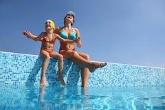 Mutter mit Tochter sitzen auf Geländer des Pools Stockfotografie