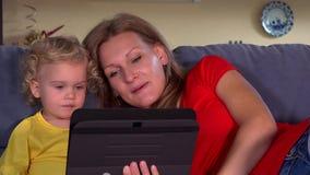 Mutter mit Tochterschlagkuß zum Vater auf Tablettenvideogespräch stock footage