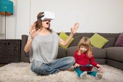 Mutter mit VR-Gläsern und -kind mit Tablette Lizenzfreie Stockfotografie
