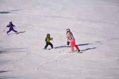 Mutter mit zwei Kinderdem ski fahren lizenzfreies stockbild