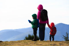 Mutter mit zwei Kindern, die in den Bergen wandern Lizenzfreies Stockbild