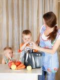 Mutter mit zwei Kindern, die Saft tun Stockbilder