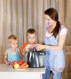 Mutter mit zwei Kindern, die Saft tun Lizenzfreies Stockfoto