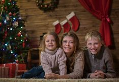Mutter mit zwei Kindern nahe dem Weihnachtsbaum stockbilder