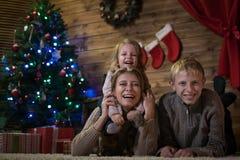 Mutter mit zwei Kindern nahe dem Weihnachtsbaum stockfotografie