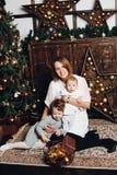 Mutter mit zwei Kindern am Weihnachtsbaum lizenzfreie stockfotos