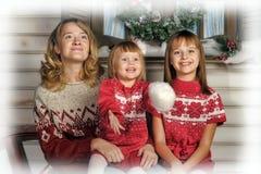 Mutter mit zwei Mädchen auf einer Bank nahe dem Haus Lizenzfreies Stockbild